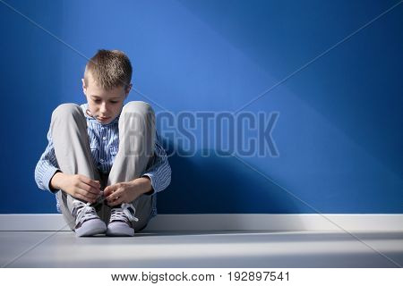 Depressed boy sitting on a floor in blue room
