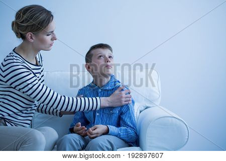 Mother and her autistic son sitting on the sofa