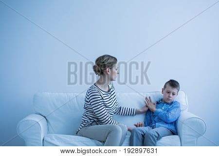 Serious mother and her autistic son sitting on a sofa