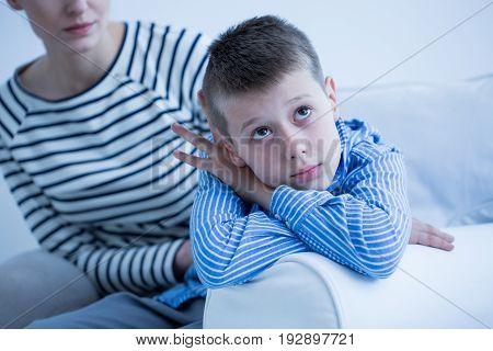Sad boy and his mom sitting on a sofa