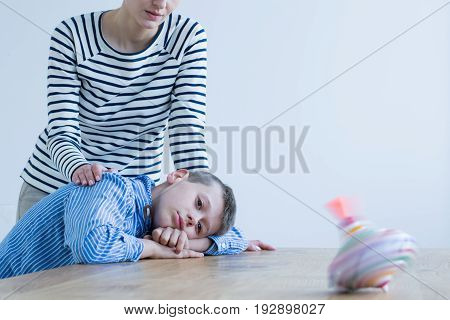 Sad boy and his mom looking at spinning top on wooden table
