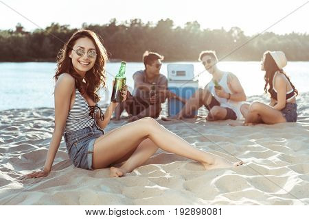 young smiling woman drinking beer while her friends resting behind on sandy beach