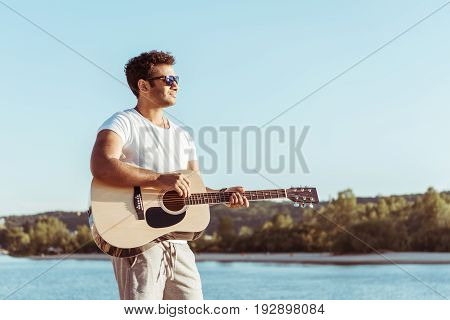 young african american man playing guitar and looking away while standing on riverside