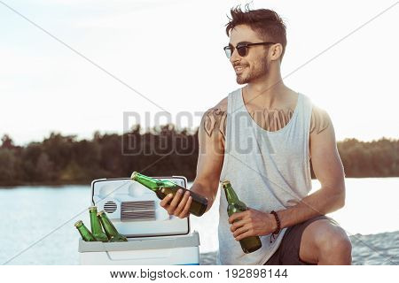 Young Casual Man In Sunglasses Holding Bottles Of Beer On Riverside