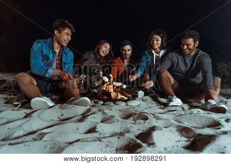 Young Smiling Multiethnic Friends Roasting Marshmallows On Bonfire At Sandy Beach