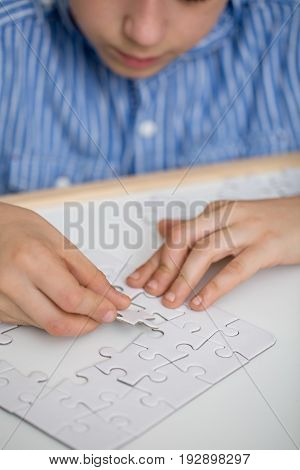 Focused boy solving a puzzle on a table