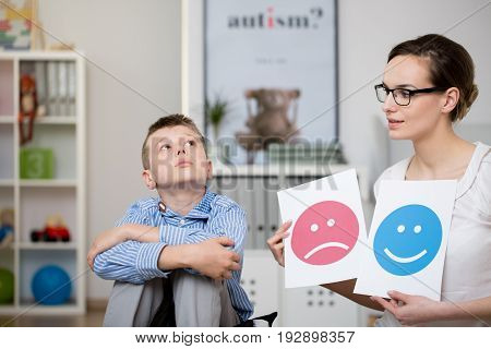 Sad autistic boy and his psychologist during a meeting