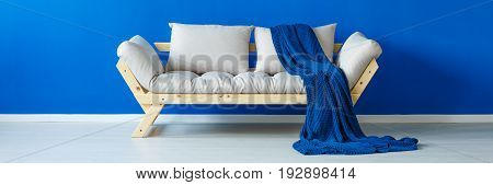Modern wooden settee on a blue wall