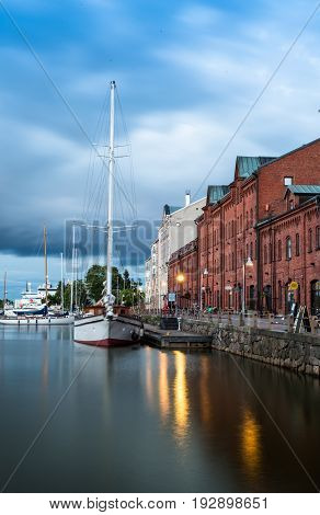 Scenic summer evening panorama of the Old Port pier architecture with tall historical sailing ships, yachts and boats in Helsinki, Finland