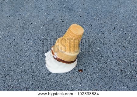 Vanilla ice cream cone dropped on concrete street or road ground with disappointment selective focus (sad concept)