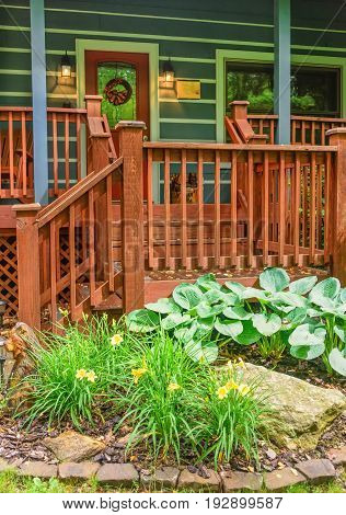 Wooden front porch of cabin with landcaping.