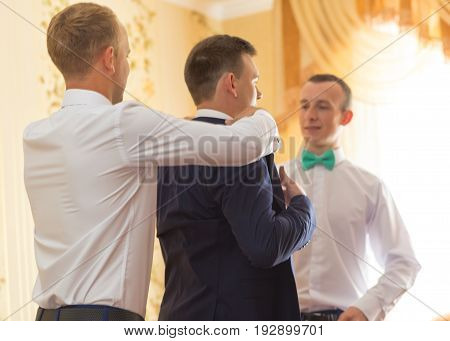 VILHIVKA UKRAINE - 21 May 2017: Groomsman helps to wear a jacket to the groom in room. Shallow depth of field.