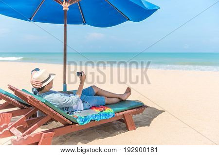 young man lying on wooden beach bench with blue umbrella and take photo of turquoise sea and beautiful sky by smartphone vacation time and summer holiday concepts digital nomad lifestyle