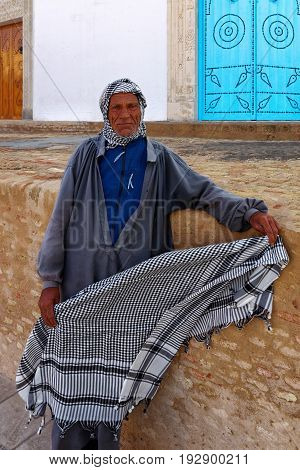 KAIROUAN, TUNISIA - OCTOBER 27, 2010: An old Muslim man selling kefia in the street of Kairouan, Tunisia.