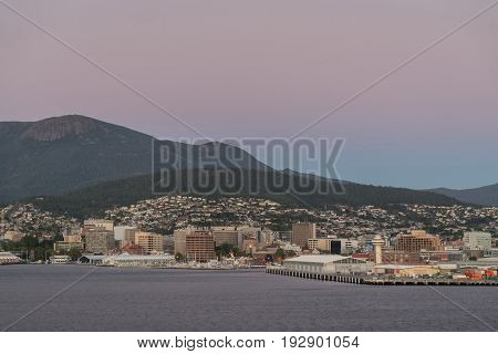Hobart Australia - March 19. 2017: Tasmania. Pink sky over the forested mountain the backdrop of downtown. The bay and the high-rises near the coastline. Houses on the hill slopes.