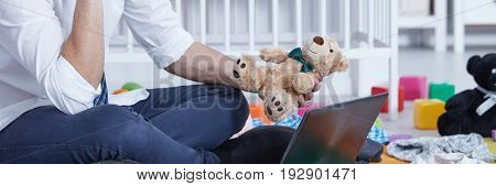 Man sitting in front of laptop screen and holding teddy bear