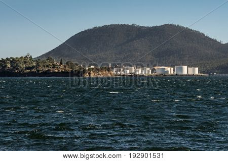 Hobart Australia - March 19. 2017: Tasmania. The Petroleum harbor with its bright white tanks across Cornelian Bay. Forested mountain in back. Blue sky and blue Derwent River water.