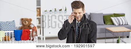 Room interior with elegant man making a phone call
