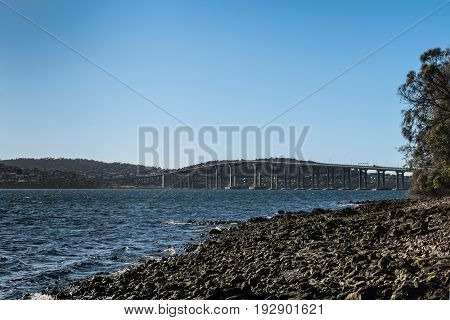 Hobart Australia - March 19. 2017: Tasmania. The long high Tasman Highway Bridge on tall pillars over Derwent River seen from Cornelian Bay beach. Blue sky mirrored in water rocky shoreline.