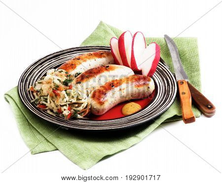 Delicious Grilled White Munich Sausages with Pickled Cabbage Chopped Radish and Mustard Sauce on Red Striped Plate isolated on White background