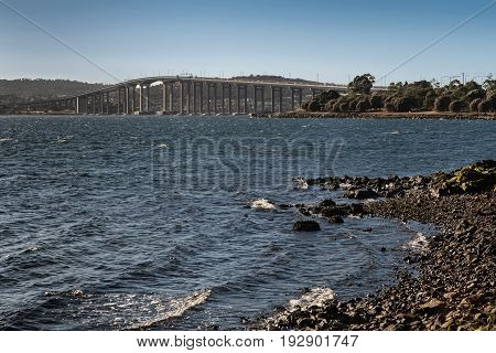 Hobart Australia - March 19. 2017: Tasmania. Closer look on the long high Tasman Highway Bridge on tall pillars over Derwent River seen from Cornelian Bay beach. Blue sky green trees at on ramp.