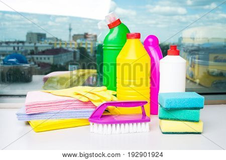 Range of cleaning products for the home. Detergents, chemical bottles, cleaning sponges and gloves. On the background of the window.