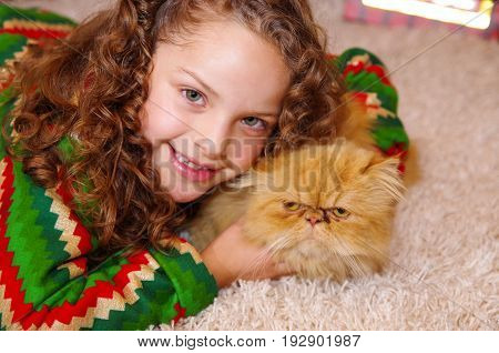 Beautiful smiling litle girl wearing a christmas clothes, hugging her yellow cat, laying on a white carpet.