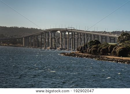 Hobart Australia - March 19. 2017: Tasmania. Closeup on the long high Tasman Highway Bridge on tall pillars over Derwent River seen from the water. Blue sky mirrored in water.