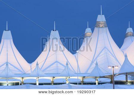 Denver International Airport at Dusk. Focus on window lit peaks