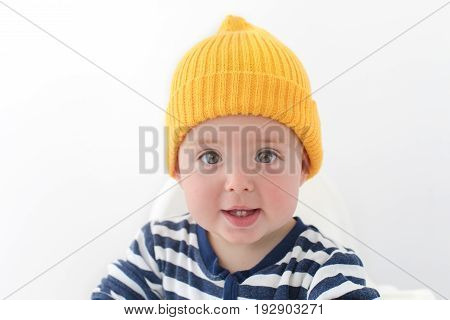 Kid in a yellow hat with two first teeth. Baby with two milk teeth smiling at the camera , studio