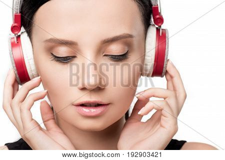 Close Up Portrait Of Attractive Girl Listening Music In Headphones Isolated On White