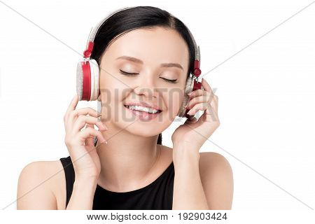 Portrait Of Young Woman With Eyes Closed Listening Music In Headphones Isolated On White