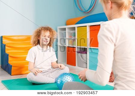 Smiling boy and a woman playing with a ball during sensory integration session