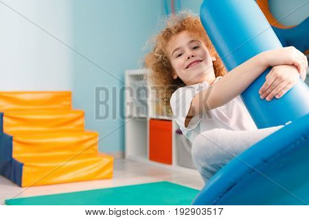 Happy boy using blue disc swing for therapy