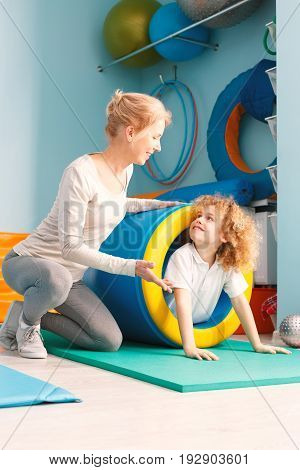 Smiling boy using sensory integration equipment and his therapist helping him