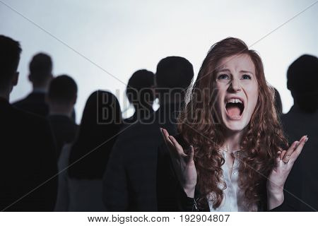 Screaming woman standing in anonymous crowd of people