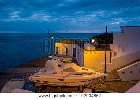 Night scene of lifted luxury motor boat illuminated by street lanterns. Marina Santiago del Teide, Canary islands, Tenerife, Spain.