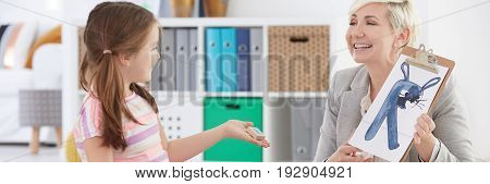 Speech therapist showing little girl funny letters on classes