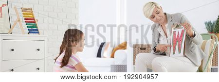 Female speech therapist leading articulation training for little girl