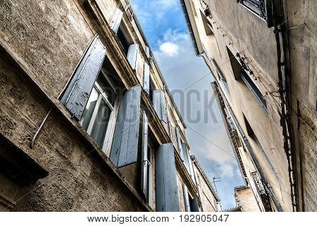 Strip of blue sky with clouds between two old french close standing buildings windows with weather beaten open shutters