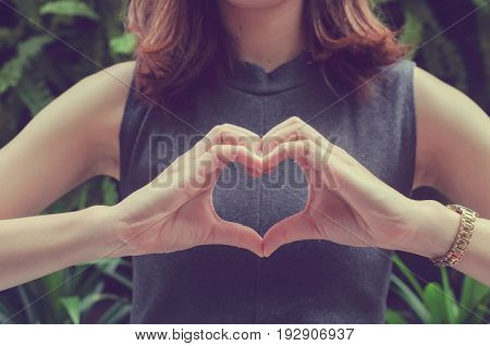 close up focus on hands girl make love shape sign on her chest:anti and heal heart attack concept for healthy life.vintage filter color