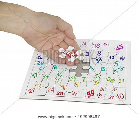 Luck and lottery numbers jigsaw puzzle - female hand holding a jigsaw piece with the word LUCK on it with a lottery numbers jigsaw beneath  isolated on white background