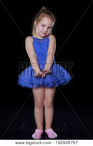 Little ballerina girl 4 years old in a blue tutu dancing in a dark room