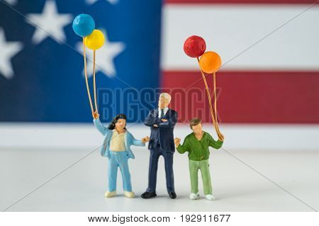 happy american miniature figure family holding balloons with United State national flag in the background as celebrating the Independence day.