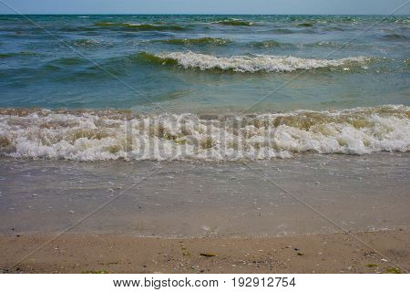 The turquoise sea waves on a sunny summer day