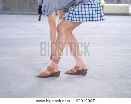Woman suffering from leg pain on street