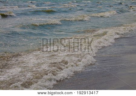 Beautiful turquoise sea waves ashore in the sunlight