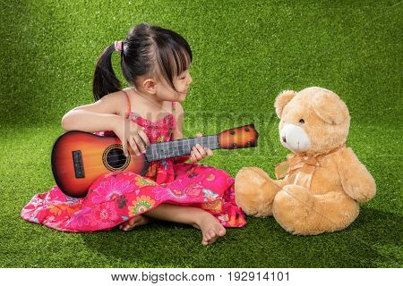 Asian Little Chinese Girl Playing Guitar With Teddy Bear
