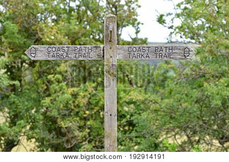 A wooden sign on the Southwest Coast Path / Tarka Trail public footpath and cycleway. Taken between Bideford and Barnstaple in North Devon England