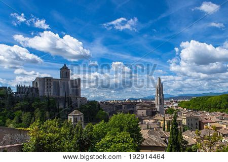 Girona, Catalinia old town view with green mountains and blue sky with clouds